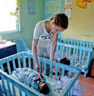 Eine Freiwillige bringt ein Kind im Sozialarbeit - Projekt ins Bett