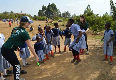 Eine Freiwillige hilft den Schülerinnen beim Seilspringen im Sport - Projekt in Kenia