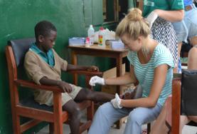 Eine Freiwillige versorgt die Schürfwunde eines jungen Patienten während ihrer Freiwilligenarbeit im Public Health-Projekt in Ghana.