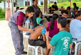 Zwei Freiwillige hören auf den Philippinen die Lunge eines älteren Patienten im Public Health - Projekt ab.