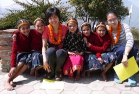 Die Kinder und einheimischen Betreuerinnen in einer Kindertagesstätte in Nepal haben sich für einen traditionellen Feiertag mit Blumenkronen geschmückt.