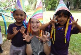 Monsteralarm in Sri Lanka! Mit selbstgebastelten Hüten spielt eine Freiwillige mit zwei Kids im Sozialarbeits - Projekt in Sri Lanka.