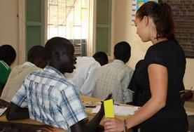 Eine Freiwillige im Mikrofinanzierungs - Projekt erklärt einem Schüler im Senegal eine Methode der Buchhaltung.