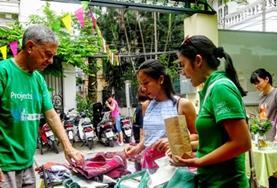 Zwei Freiwillige schlendern über den Kunstgewerbemarkt im Dorf Mai Chau, wo sie ihr Wirtschaftspraktikum absolvieren.