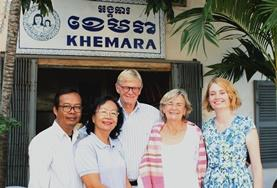 Unsere Freiwillige Prue steht mit einer Familie vor deren eigenem kleinen Geschäft in Phnom Penh, dass sie mithilfe unserer Microfinance - Förderung aufgebaut haben.