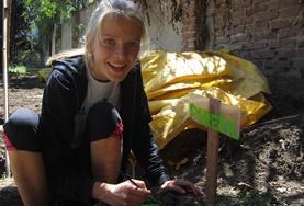 Eine Freiwillige im ökologischen Farming - Projekt lockert den Boden im Gemüsegarten des Projekts.