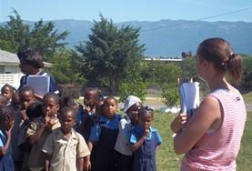 Eine Schulklasse in einer Grundschule auf Jamaika bekommt von einer Freiwilligen ein Training für den Fall einer Naturkatastrophe vor Ort.