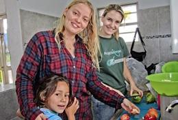 Gemeinsam kochen unsere Freiwilligen im Ernährungs - Projekt zusammen mit einem Mädchen im Pflegezentrum für fehlernährte Kinder in Bolivien.