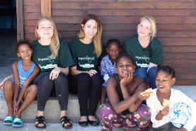 Freiwillige und junge Mädchen in Kapstadt sitzen in der Pause vom Ernährungs - Workshop auf der Veranda eines Gemeindezentrums.
