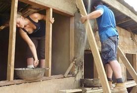 Im Hausbau - Projekt in Ghana setzen zwei Freiwillige die Rahmen für Fenster in einem neu errichteten Klassenraum.