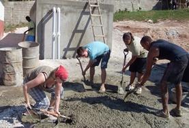 Zusammen bauen Hausbau -Freiwillige den Rahmen für ein neues Klettergerüst im Schulhof der Christiana Leased Primary School in Jamaika auf.