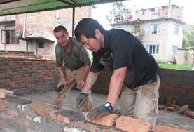 Durch Teamwork zweier Freiwilliger entsteht die Ziegelwand eines neuen Klassenzimmers in unserem Hausbau - Projekt in Nepal.