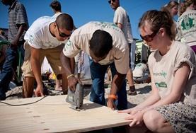 Freiwillige im Hausbau - Projekt in Südafrika sägen eine Planke zurecht, die beim Bau einer frischen Wand benötigt wird.