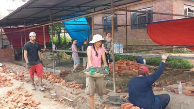 Katastrophenhilfe - Freiwillige bringen Mörtel und Ziegeln für einen neuen Klassenraum herbei