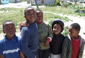 In einer Grundschule in Kapstadt gibt ein Freiwilliger zwei Schülerinnen Anleitungen zur Recherche im Internet.