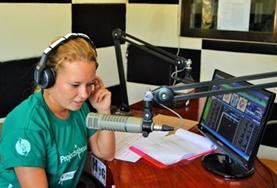 Eine Freiwillige spricht im Radiostudio in Bogo City einen Betrag ein.