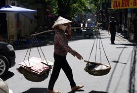Eine Frau mit Reis Hut überquert die Straße mit Vorräten für ihren Marktstand.
