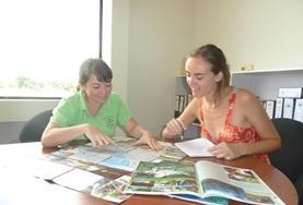 Eine Praktikantin geht im Journalismus - Projekt in Costa Rica zusammen mit ihrer Mentorin die Themenliste der letzten Ausgaben durch.