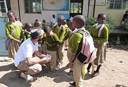 Ein Freiwilliger im Journalismus - Praktikum lernt eine Gruppe von Grundschulkindern in Arusha kennen.
