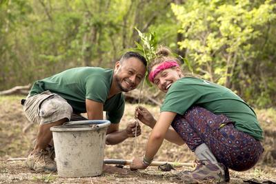 Freiwillige auf ihrer Jugendreise pflanzt zusammen mit unserm Projektleiter einen Setzling im Nationalpark