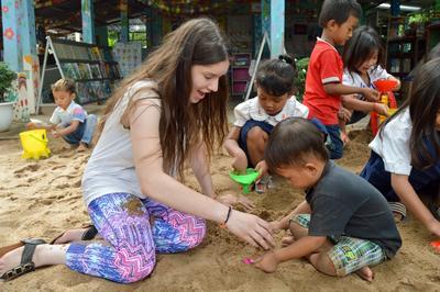 Freiwillige spielt auf der Jugendreise in Kambodscha mit einem einheimischen Kind im Sozialarbeits – Projekt