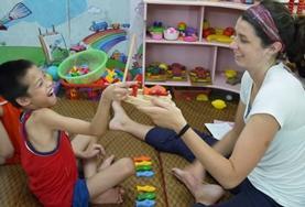Ergotherapie  Praktikantin behandelt einen jungen Patienten in Vietnam.