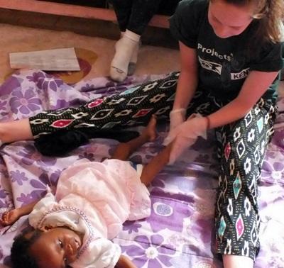 Freiwillige behandelt kleinen Patienten im Ergotherapie – Praktikum in Kenia