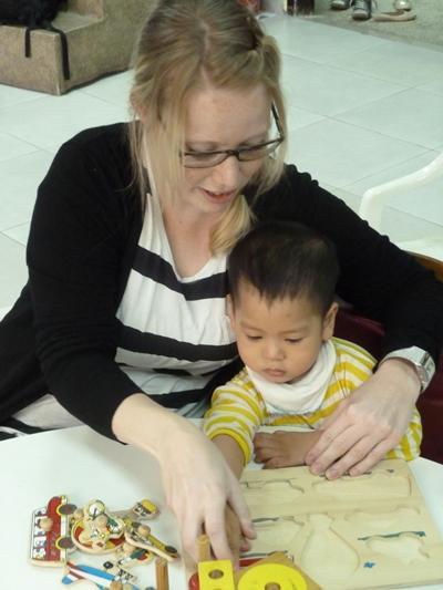 Freiwillige behandelt ein Kind im Ergotherapie – Praktikum in Vietnam