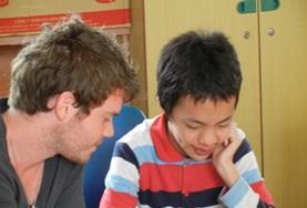 Ein Freiwilliger übt mit einem jungen Patienten die Aussprache verschiedener Vokale im Logopädie - Praktikum in Vietnam.