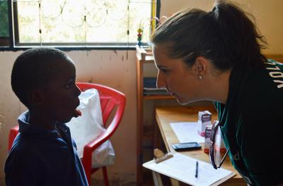 Eine Freiwillige übt eine Schlucktechnik mit einem kleinen Patienten im Logopädie - Praktikum in Tansania