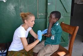 Eine Freiwillige versorgt die Armwunde eines kleinen Jungens während des Medical Outreach im Medizin - Praktikum.