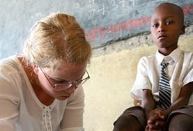 Dieser Junge bekommt während eines Medical Outreach -Tags in einer Dorfschule die Platzwunde an seinem Knie von einer Freiwilligen im Medizin - Praktikum verbunden.