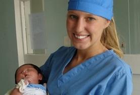Im Kreissaal einer Klinik in Ulan Bator hält eine Freiwillige im Medizin - Praktikum ein Neugeborenes in den Armen.
