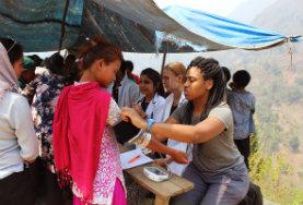 Freiwillige im Medizin - Praktikum nehmen Gesundheitsdaten wie Blutdruck und Gewicht während eines Medical Outreaches im ländlichen Nepal auf.