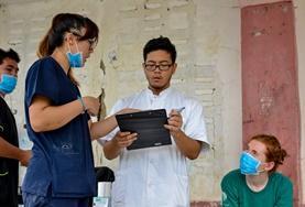 Eine Freiwillige lauscht im Medizin-Praktikum auf den Philippinen einem Gespräch des Fachpersonals.