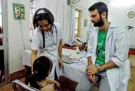 Während der Behandlung eines Kindes beobachtet unser Freiwilliger im Medizin - Praktikum die Methode der leitenden Ärztin.
