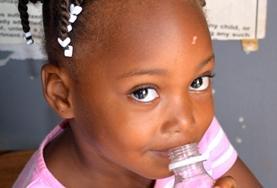 Ein Kind besucht einen von Projects Abroad organisierten Medical Outreach in Belize, wo unsere Freiwilligen auch gesundes Essen und Wasser verteilen.