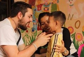 In einem Kindergarten in Kambodscha untersucht ein Medizin - Student als Freiwilliger im Public Health - Praktikum einen jungen Patienten.