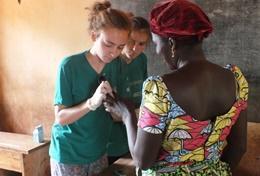 Eine Freiwillige ermittelt den Blutzuckerspiegel einer Dorfbewohnerin bei einem Check-up im Public Health - Praktikum in Togo.