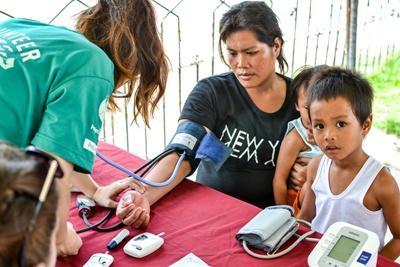 Eine Freiwillige misst den Blutdruck einer Frau auf den Philippinen