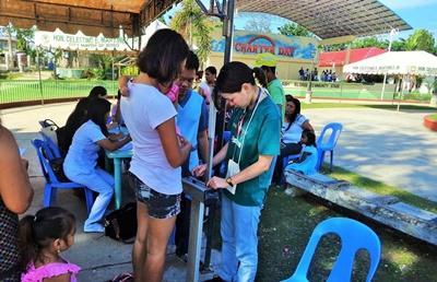 Eine Freiwillige wiegt eine junge Frau im Public Health Projekt auf den Philippinen