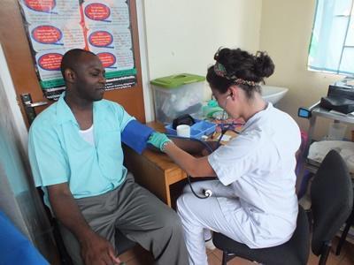 Freiwillige misst den Blutdruck eines Patienten im Medizin-Praktikum in Jamaika