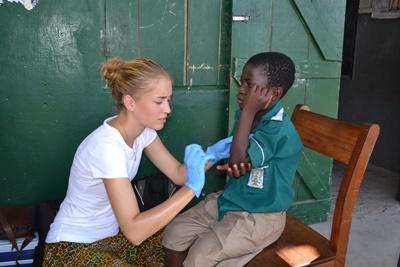 Freiwillige versorgt einen kleinen Patienten im Medizin – Praktikum in Ghana