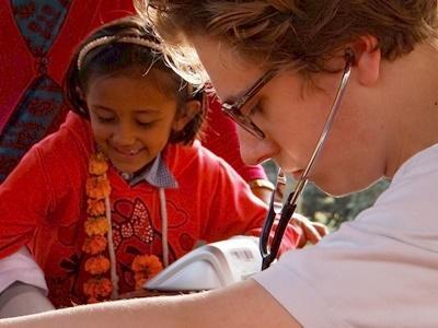 Freiwilliger untersucht Kind im Medizin – Praktikum in Nepal, Asien