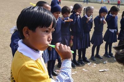 Kinder putzen sich im Rahmen der Medizin-Kampagne die Zähne
