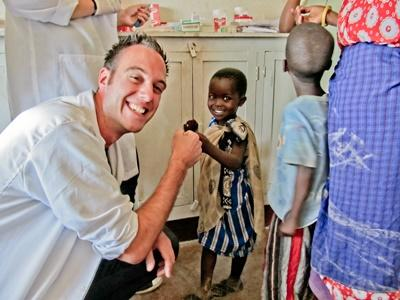 Freiwilliger mit einem fröhlichen kleinen Patienten in Tansania