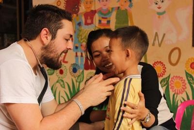 Ein Freiwilliger überprüft die Zähnchen eines Kindes im Public Health - Projekt