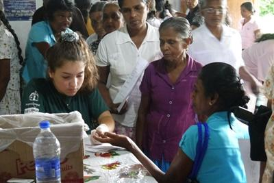 Eine Freiwillige misst den Blutzucker einer Frau in Sri Lanka
