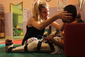 Vorsichtig richtet eine Praktikantin die Haltung eines jungen Patienten im Physiotherapie - Praktikum in Kambodscha.