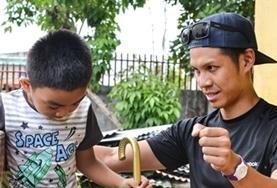 Physiotherapie-Praktikant bei einer Therapiesitzung mit einem jungen Patienten auf den Philippinen, der Unterstützung beim Laufen braucht.